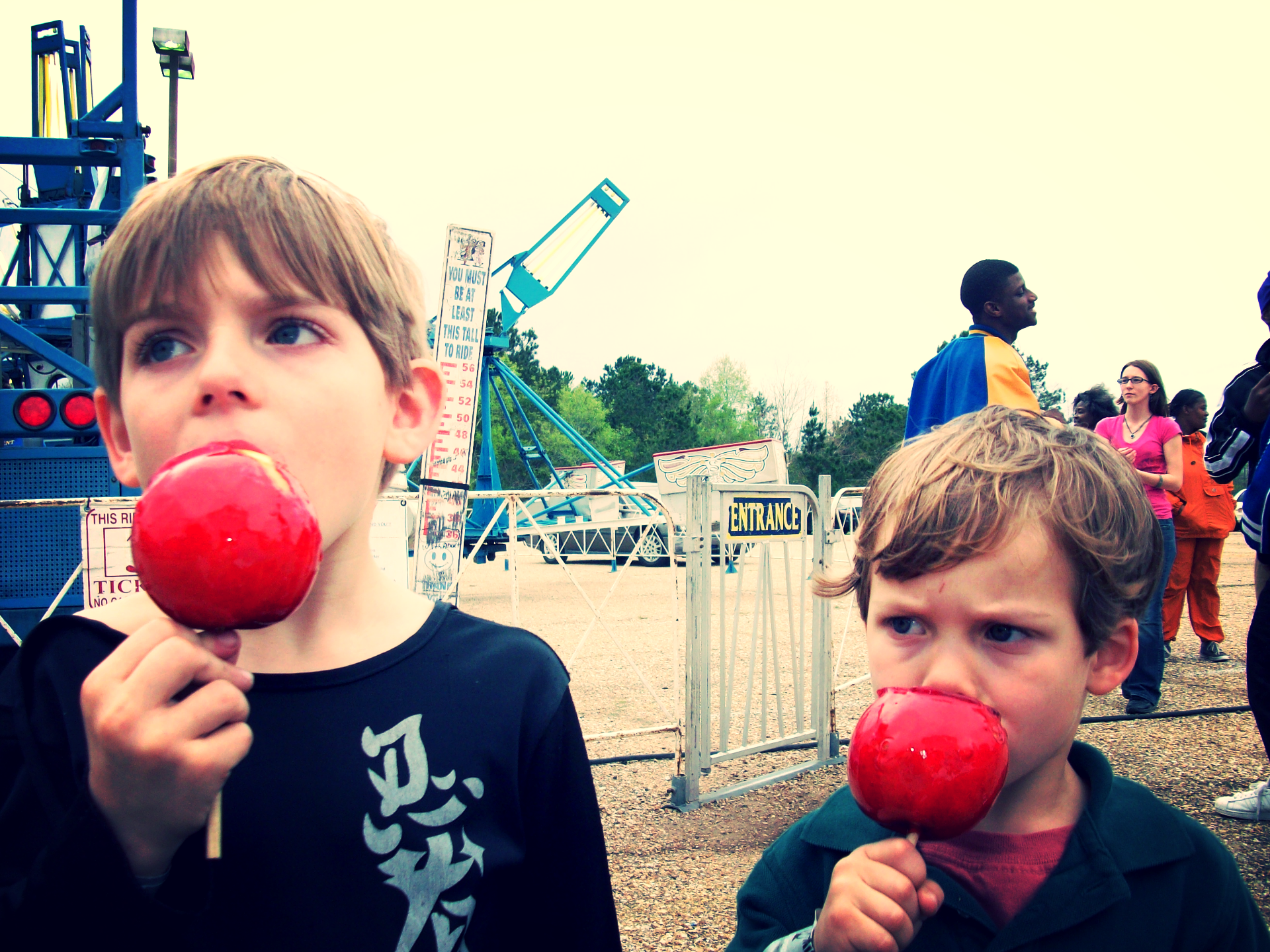 2 young boys enjoy a candy apple