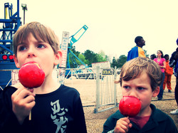 2 young boys enjoy a candy apple