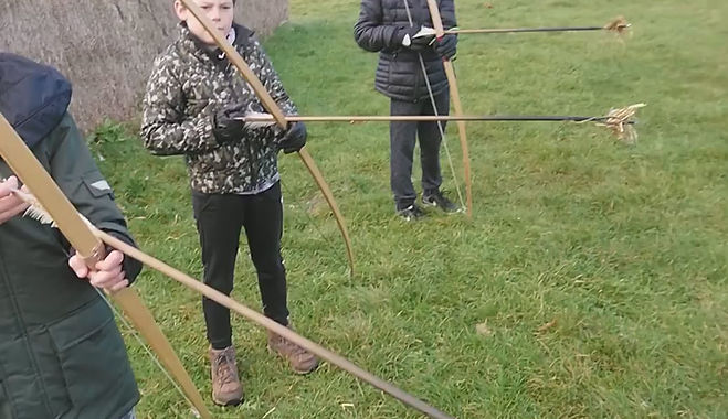 Three children shooting fire arrows with the help of a coach