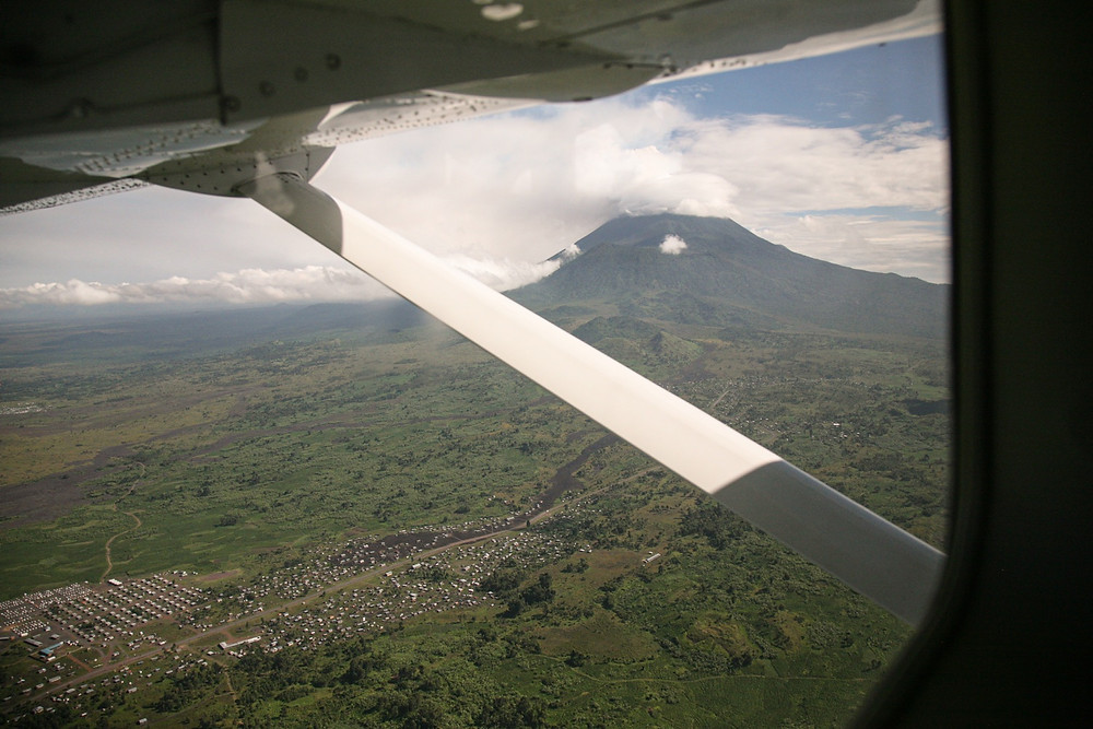 Mt. Nyiragongo spewing ash while we come in to land in Goma. Lava trails from previous eruptions can be seen cutting through the forest.