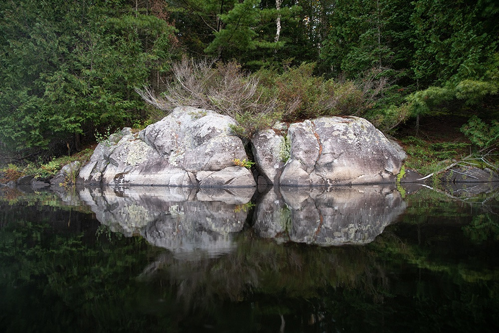 A rock face reflecting on a lake in the early morning.