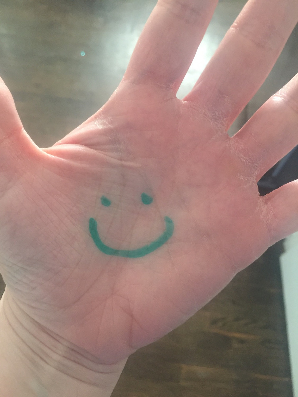Palm with green marker smiley for World Adoption Day