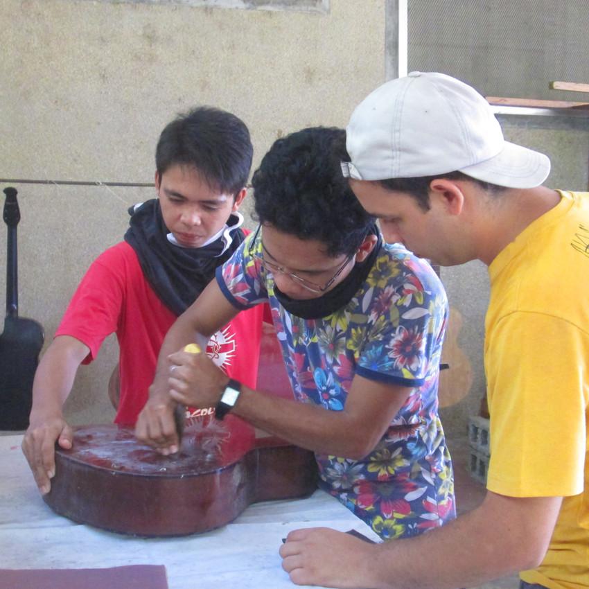 Seminarians learning how to repair guitars