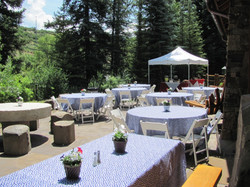"""Star pattern cloths over 60"""" rnd tables and white wood chairs"""