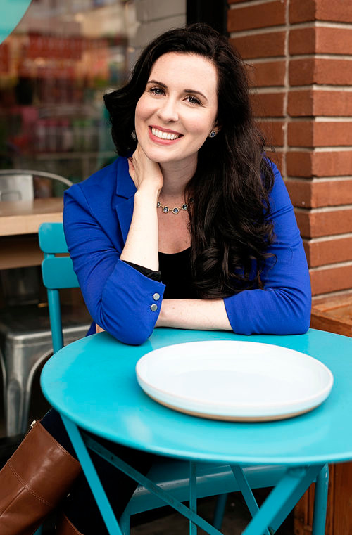 image of lauren a white brunette sitting at a cute blue cafe table, smiling