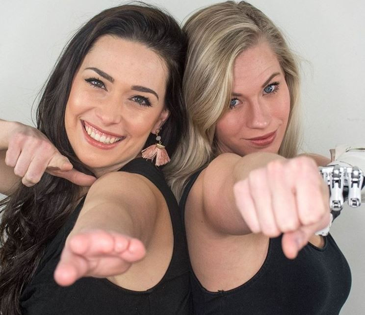 image shows disarming disability hosts nicole and sarah smiling and pointing towards the camera with their limb differences shown