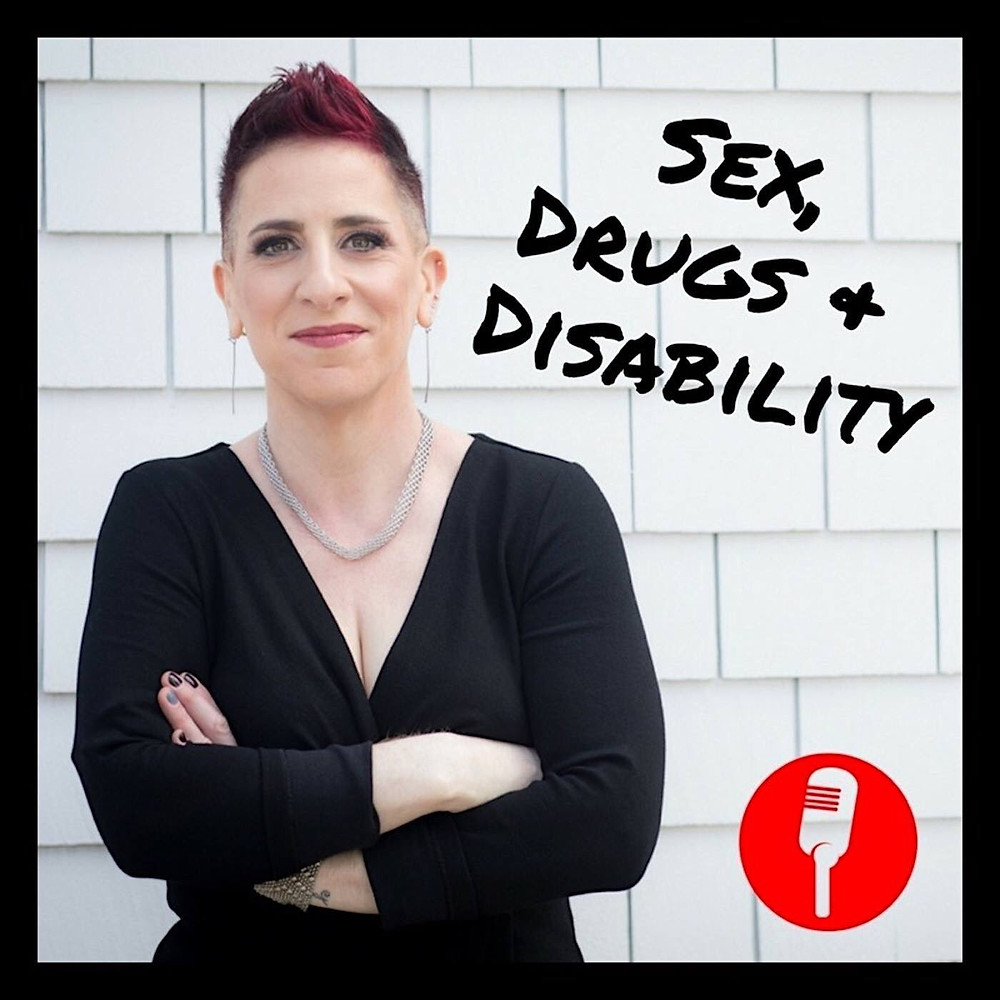 image shows podcast host julie with arms crossed, wearing a black dress with a red short mohawk.