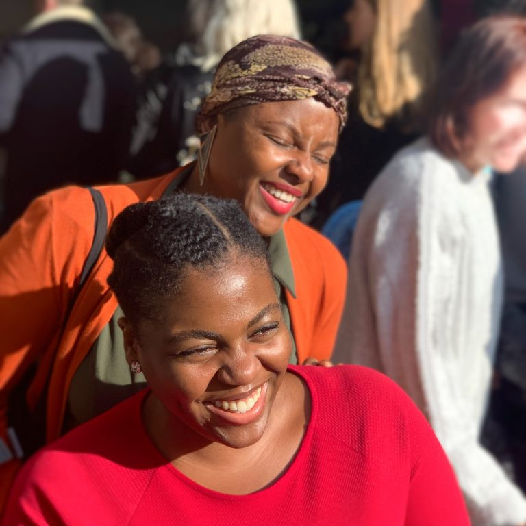 image shows two black femmes in the sun smiling with melanin popping