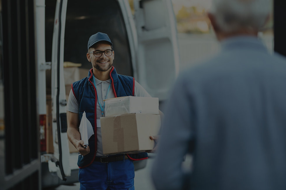 Happy deliverer carrying packages while making home delivery to his customer_edited.jpg