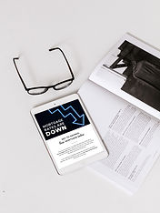 Image of glasses and a tablet sitting on an open book. On the tablet is an email about mortgage rates.