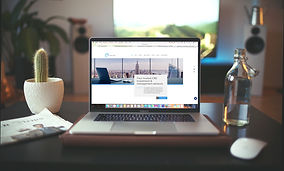 Image of a laptop sitting on a desk showing a mortgage company home page