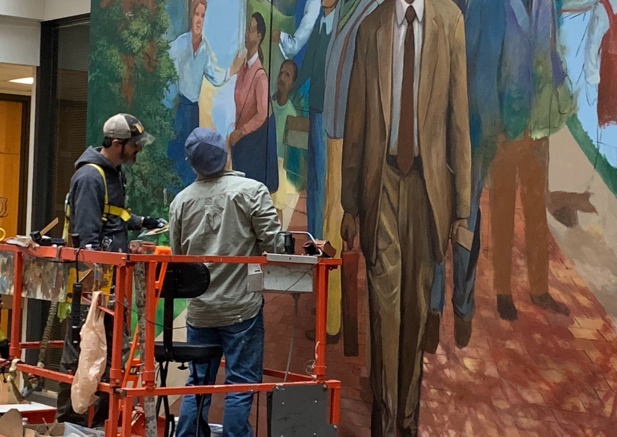 Robert Dafford and teammember work on mural