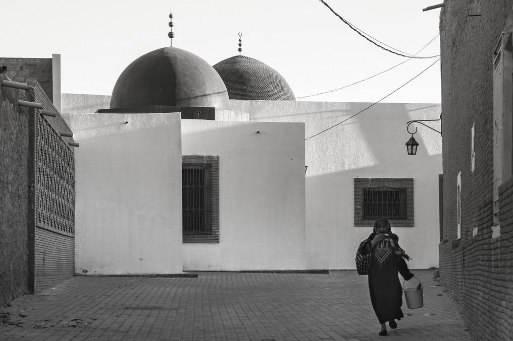 Tozeur Medina Frau mit Einmer sw (1 von