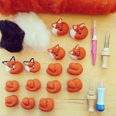 needle felt foxes being made with needle felting tools and wool