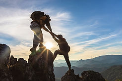 Silhouette Two Male hikers climbing up mountain cliff and one of them giving helping hand.