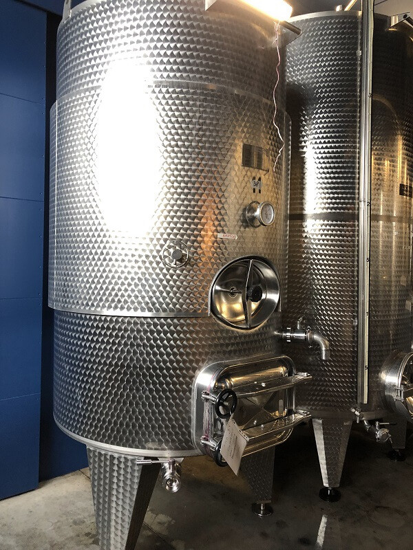 stainless steel fermentation tank for production of Moscato d'Ast at Gianni Doglia winery during a wine tasting tour in Piedmont