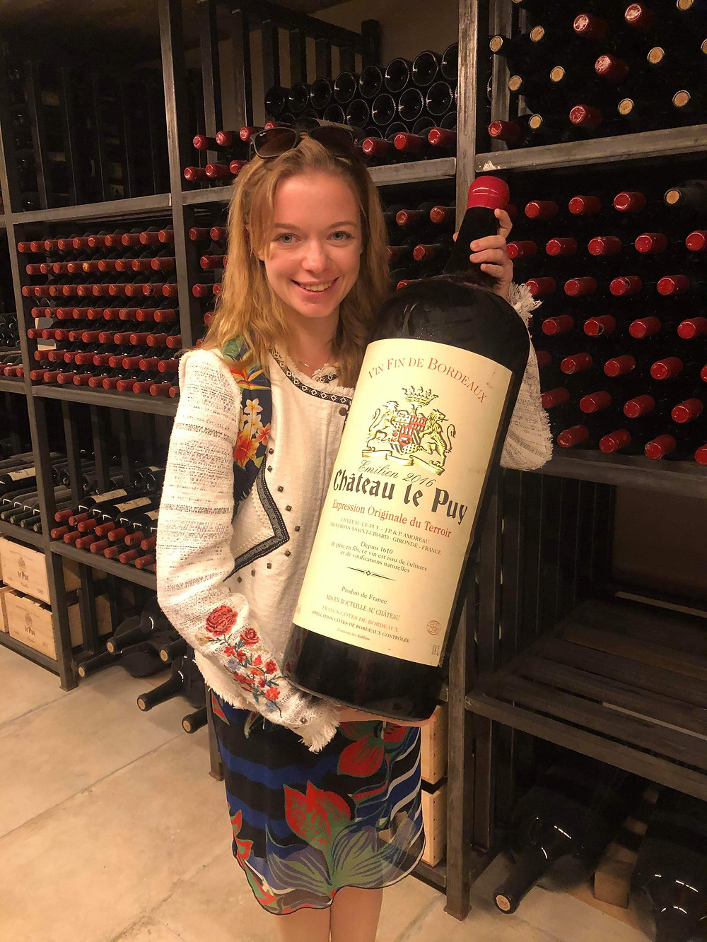 with a huge bottle in hands in the wine library of Chateau Le Puy