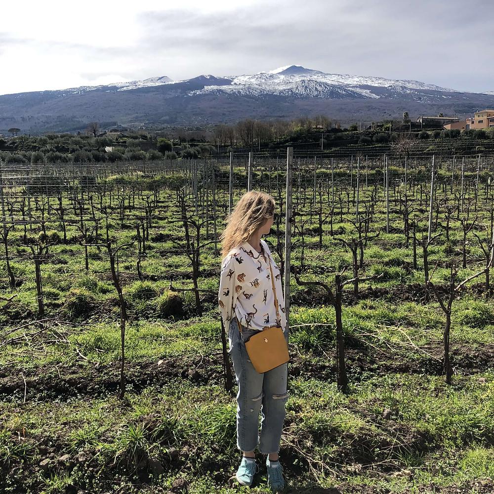 wine blogger in Tenuta delle Terre Nere Calderara Sottana vineyard with Etna volcano view in Sicily