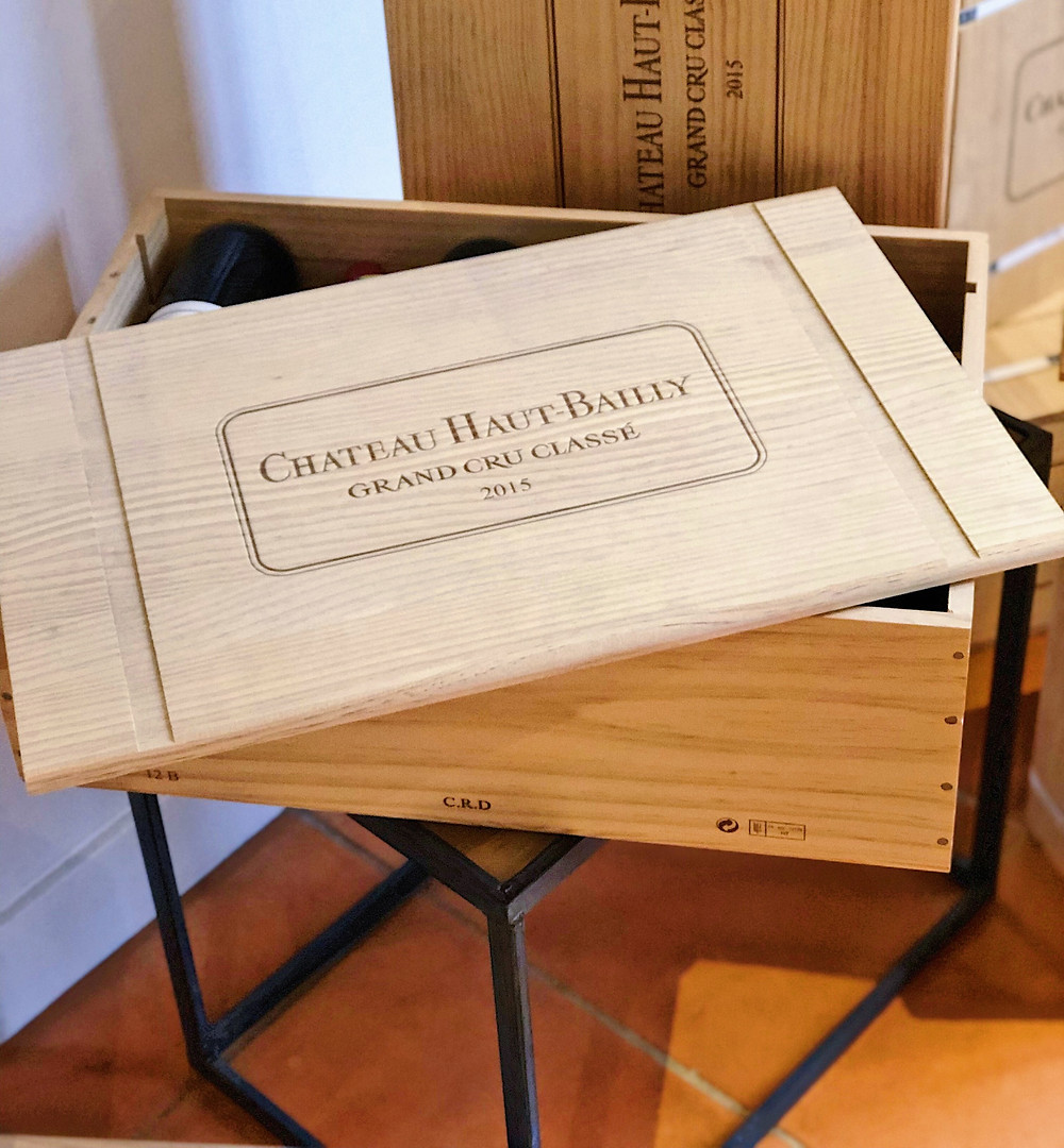 case of Bordeaux wine bottles in Chateau Haut Bailly during wine tour to Graves Pessac Leognan wine region