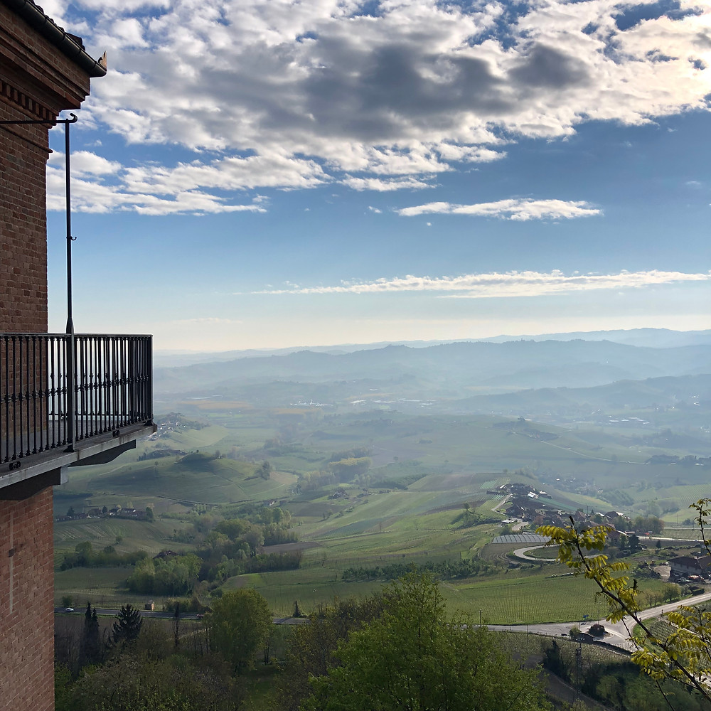 View over the Barolo vineyards from La Morra town centre in the early morning with mist and clouds
