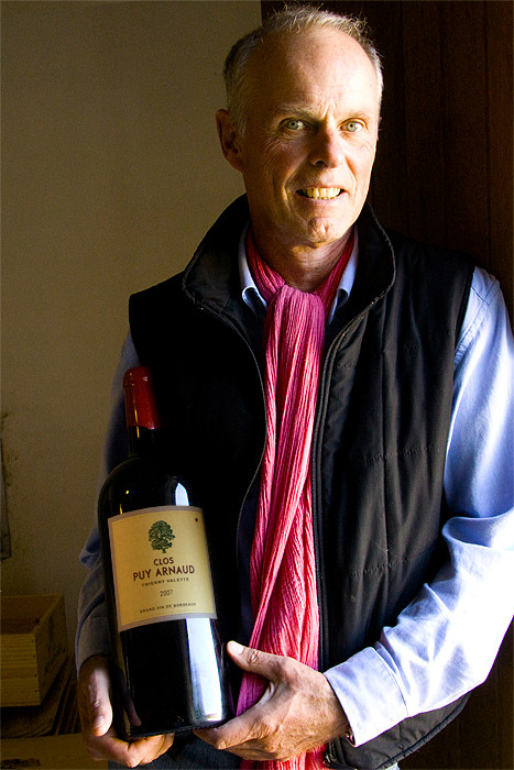 Thierry Valette holding a bottle of Clos Puy Arnoud in his winery in Castillon Bordeaux