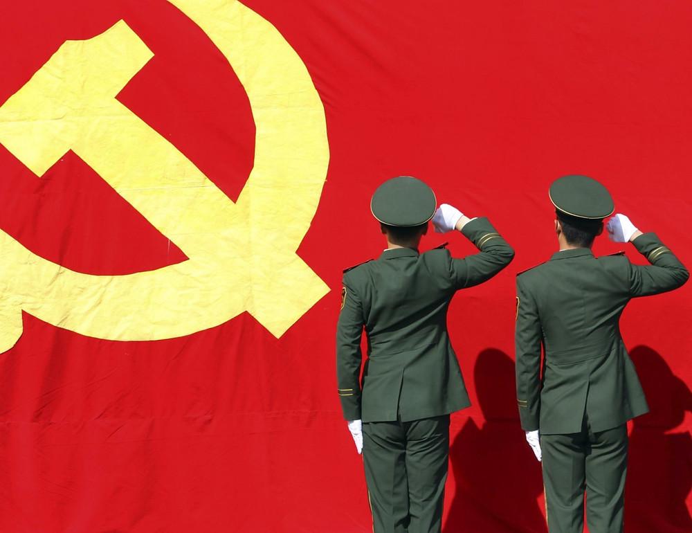 Militares fazem continência diante da bandeira da República Popular da China
