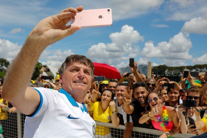 O presidente Bolsonaro faz selfie em manifestação de apoio