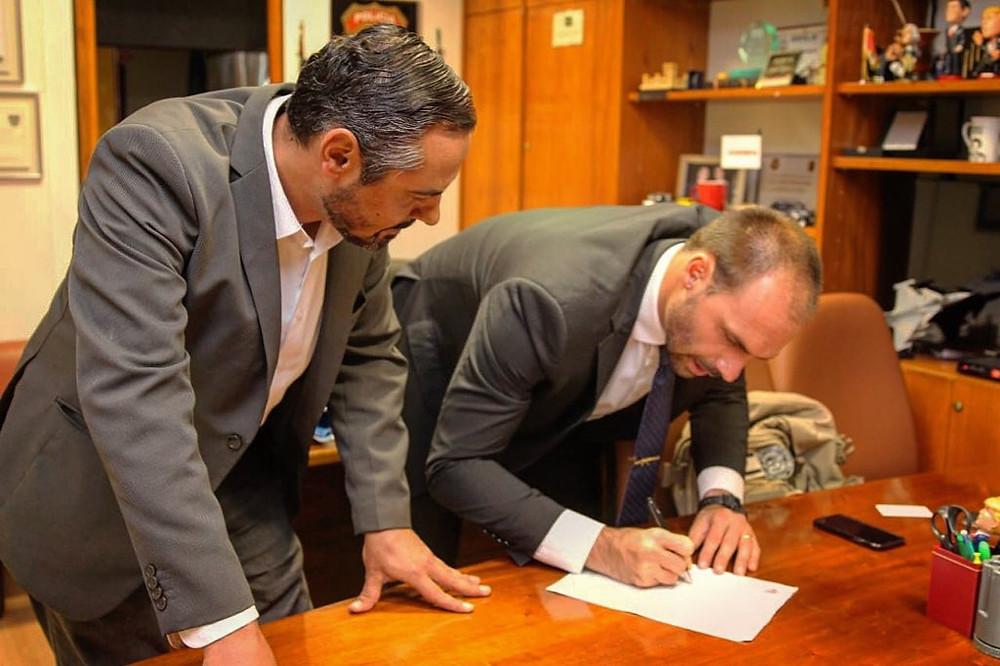 El diputado Eduardo Bolsonaro, a la derecha, firma un requerimento para investigar al Foro de São Paulo; a la izquierda Maciel Joaquim, coordinador de la asociación Frente Ciudadana