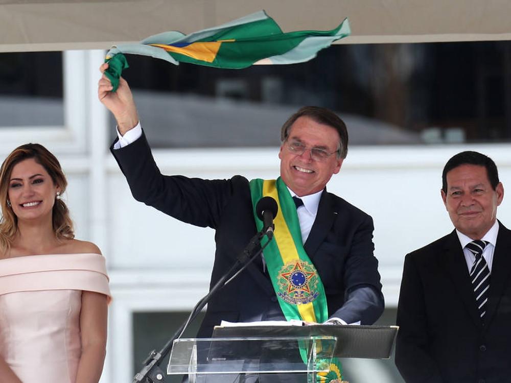 Bolsonaro ondea la bandera brasileña en su discurso al pueblo, fuera del Palacio de Planalto