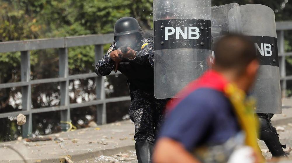 Um agente da Policia Nacional Bolivariana dispara contra um manifestante venezuelano