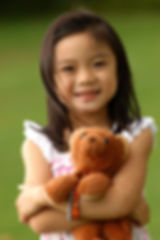 Image of a young Asian girl holding her teddy bear