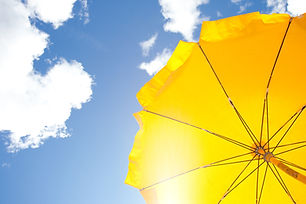 yellow umbrella on blue sky with clouds.
