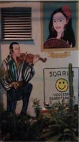 Muro pintado com Mio Vacite tocando violão para sua amada na janela, a saudosa cigana Liz Vacite