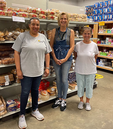 Manager and volunteers in the food pantry bread aisle
