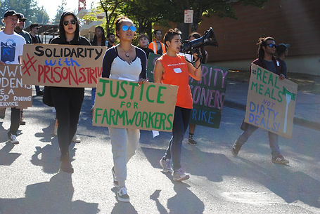 Multiracial group of student activists march and carry signs calling for food jutice