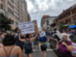 a crowd marches against traffic in downtown Boston, one demonstrator holds up a large sign advertizing the Spanish simultaneos interpretation line