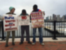 three students, one white, one person of color, hold signs advocating for a living wage. Boston city skyline behind and to the right