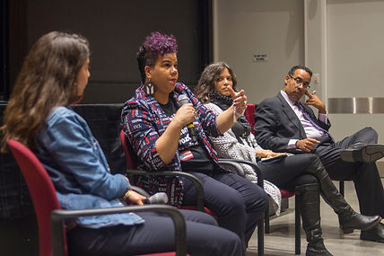 Rosa Clemente, a Black Boricua with short black and magenta hair holds a microphone. She gestures toward the audience while 3 co-panelists look on