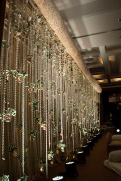 Hanging candles, fairy lights and flowers for a floral stage backdrop