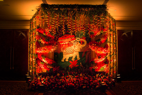 Front view of the elephant backdrop and floral installation with a flower garden in front