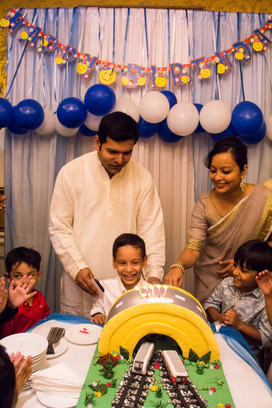 Parents overlook an overjoyed chlid cutting a birthday cake with elegant party decoration