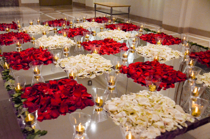 Table decoration with white and red rose petals, mirror and candles.