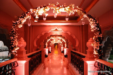 Floral arches connecting a bridge passage at a wedding in Bangalore