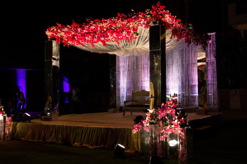 A floral mandap for an Indian wedding with mirror panels and red flowers in Bangalore