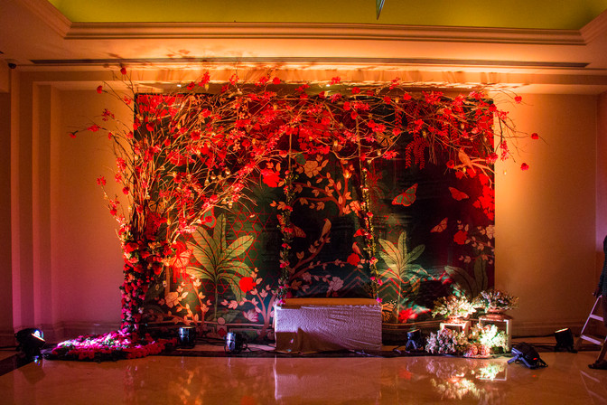 A floral photobooth with a jungle print fabric, a tree and a swing for a wedding ceremony in India