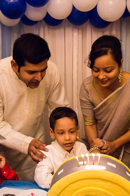 Parents helping their child cut his birthday cake