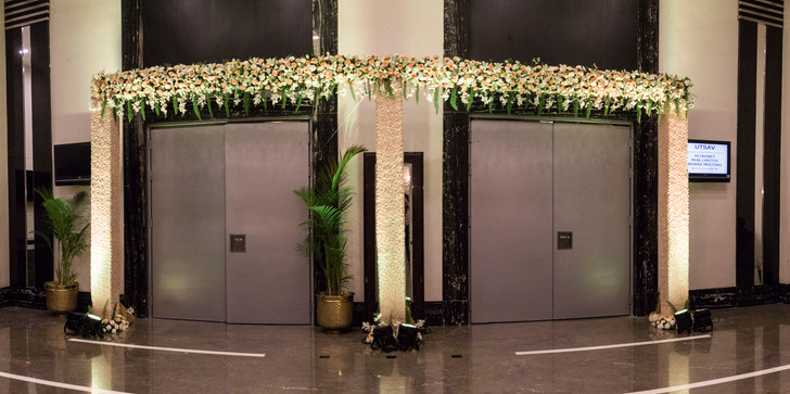 Floral entrance decoration with three pillars and a band of flowers
