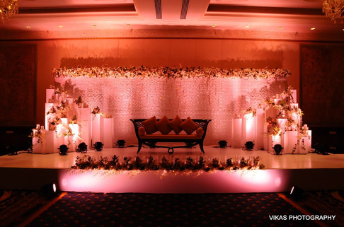 Floral backdrop with pillars, flowers and candles for a reception ceremony.