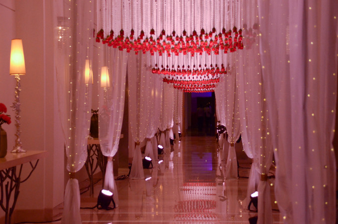 A tunnel passage with hundreds of hanging roses and fairy lights at a wedding in Bangalore