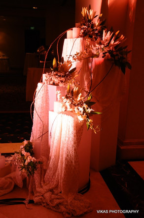 Three pillar floral installation with fabric at a wedding function